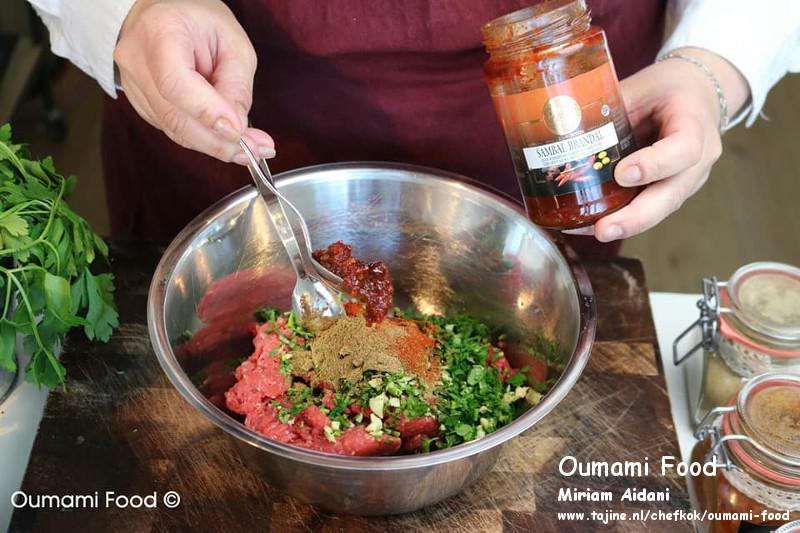 Gehaktbroodjes met pesto en cheddarkaas kruiden en sambal toevoegen aan gehakt